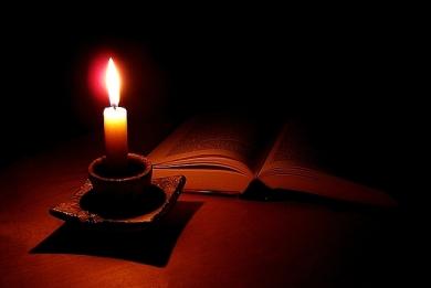 paląca się świeca i ksiązka